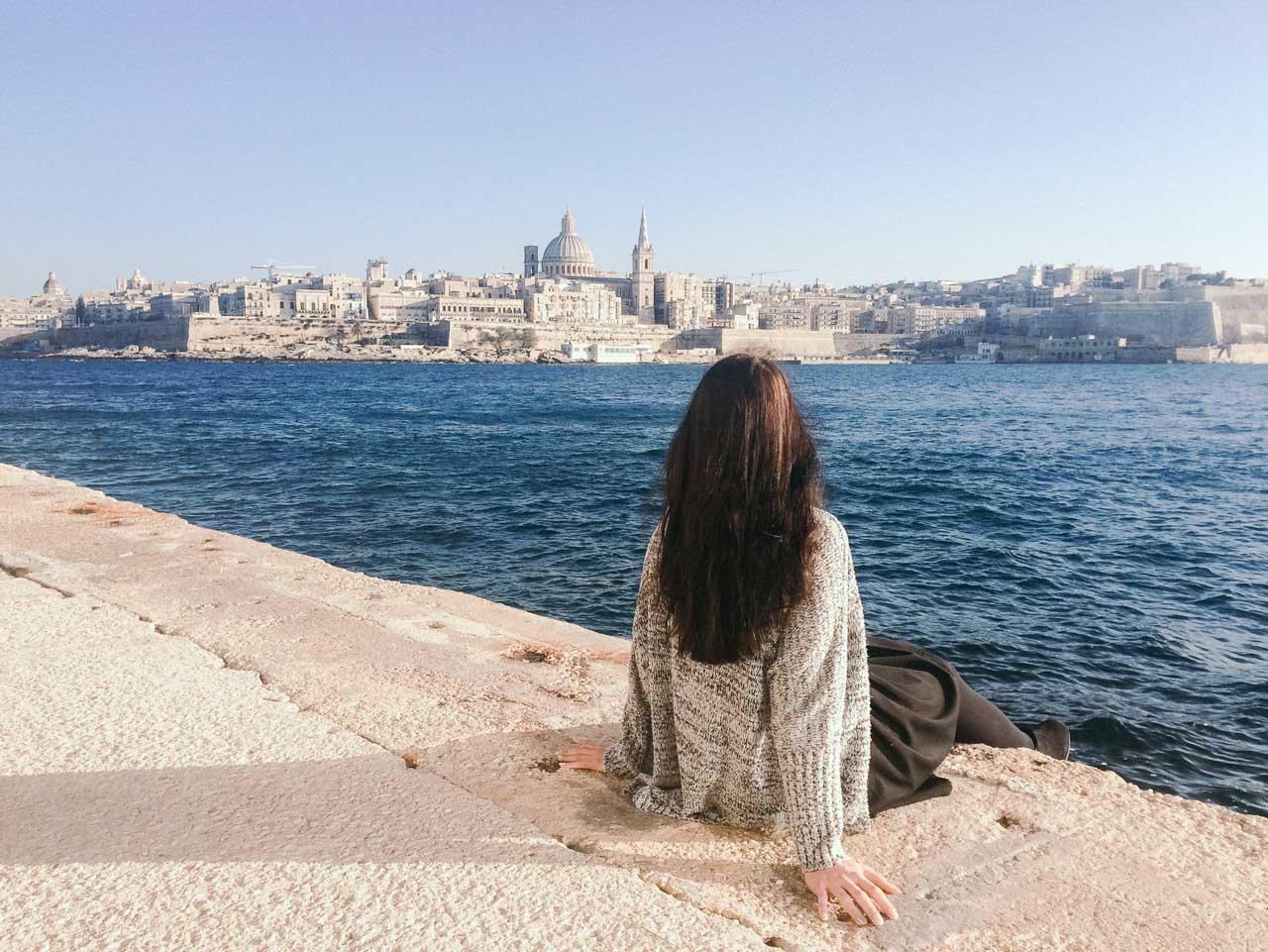 A girl sitting on the waterfront in Sliema, Malta overlooking Valletta