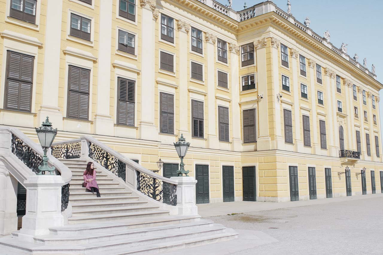 A girl sitting on the steps of the Schönbrunn Palace in Vienna, Austria