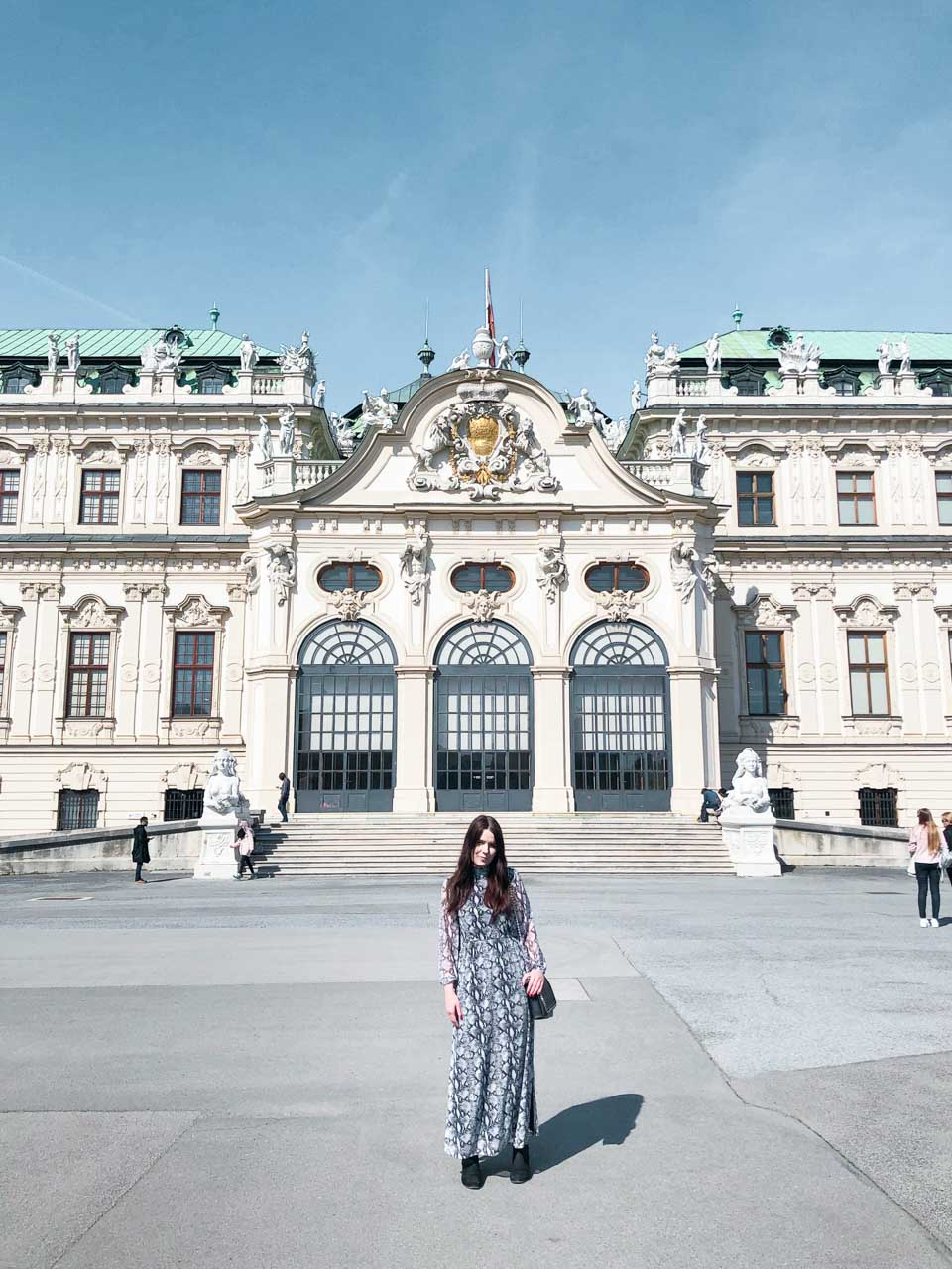 A girl in an animal print dress standing outside the Belvedere Palace in Vienna, Austria