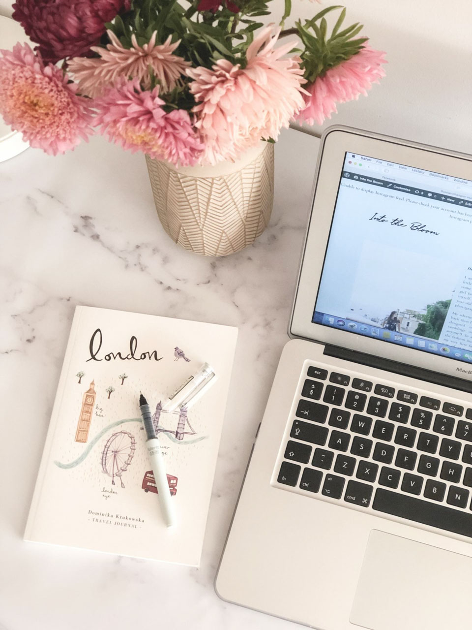 A travel journal, a vase with fresh flowers and a laptop on a marble desk