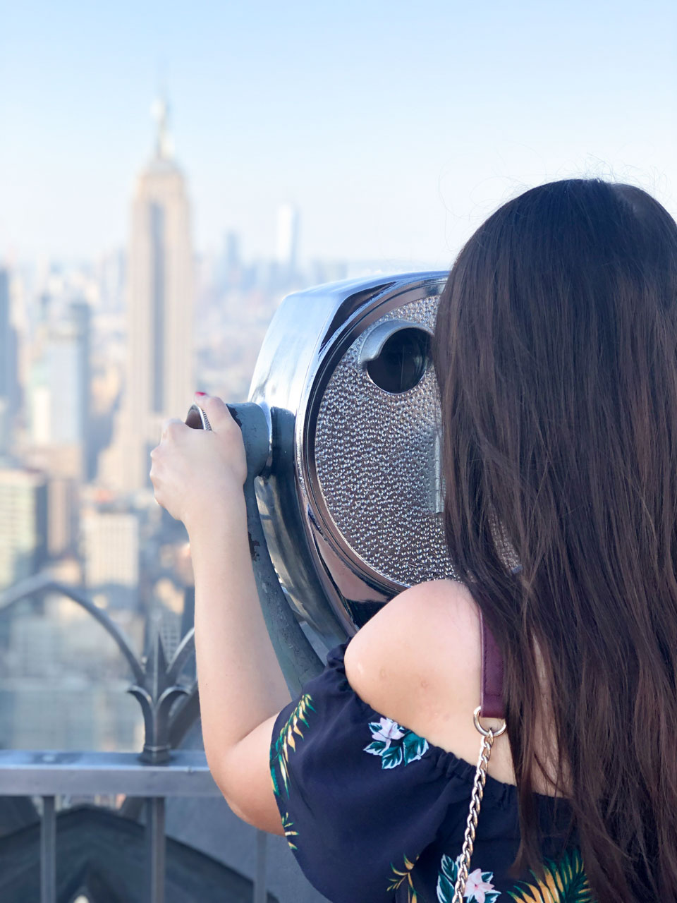A girl looking through the binoculars on Top of the Rock