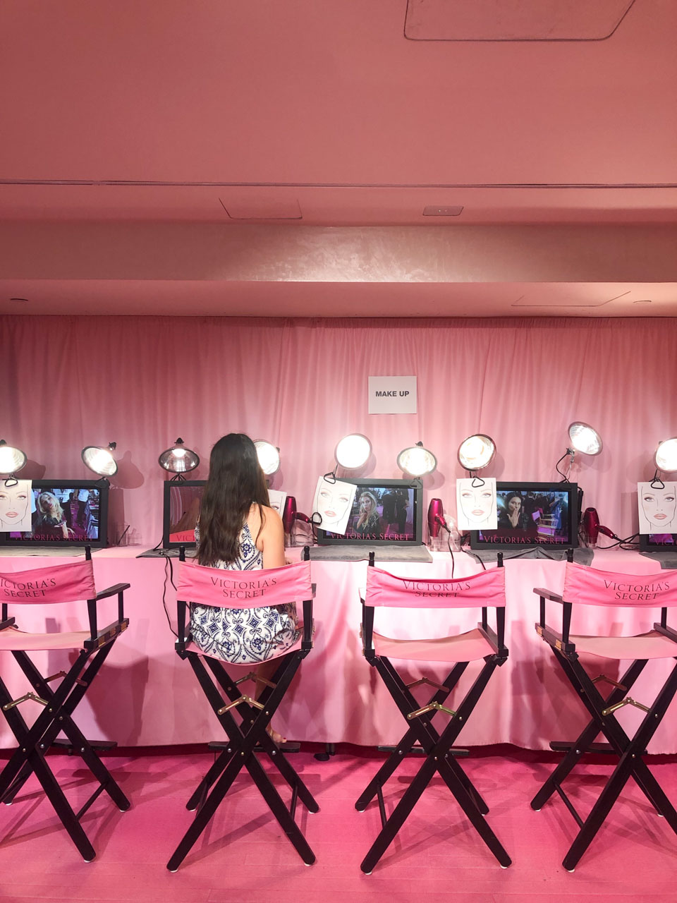 A girl in a patterned dress sitting in a makeup chair inside the Victoria's Secret Fifth Avenue store