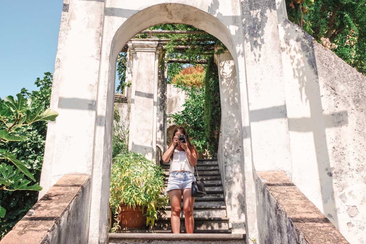 A girl pointing her camera at the photographer on the steps of Giardino della Minerva in Salerno, Italy