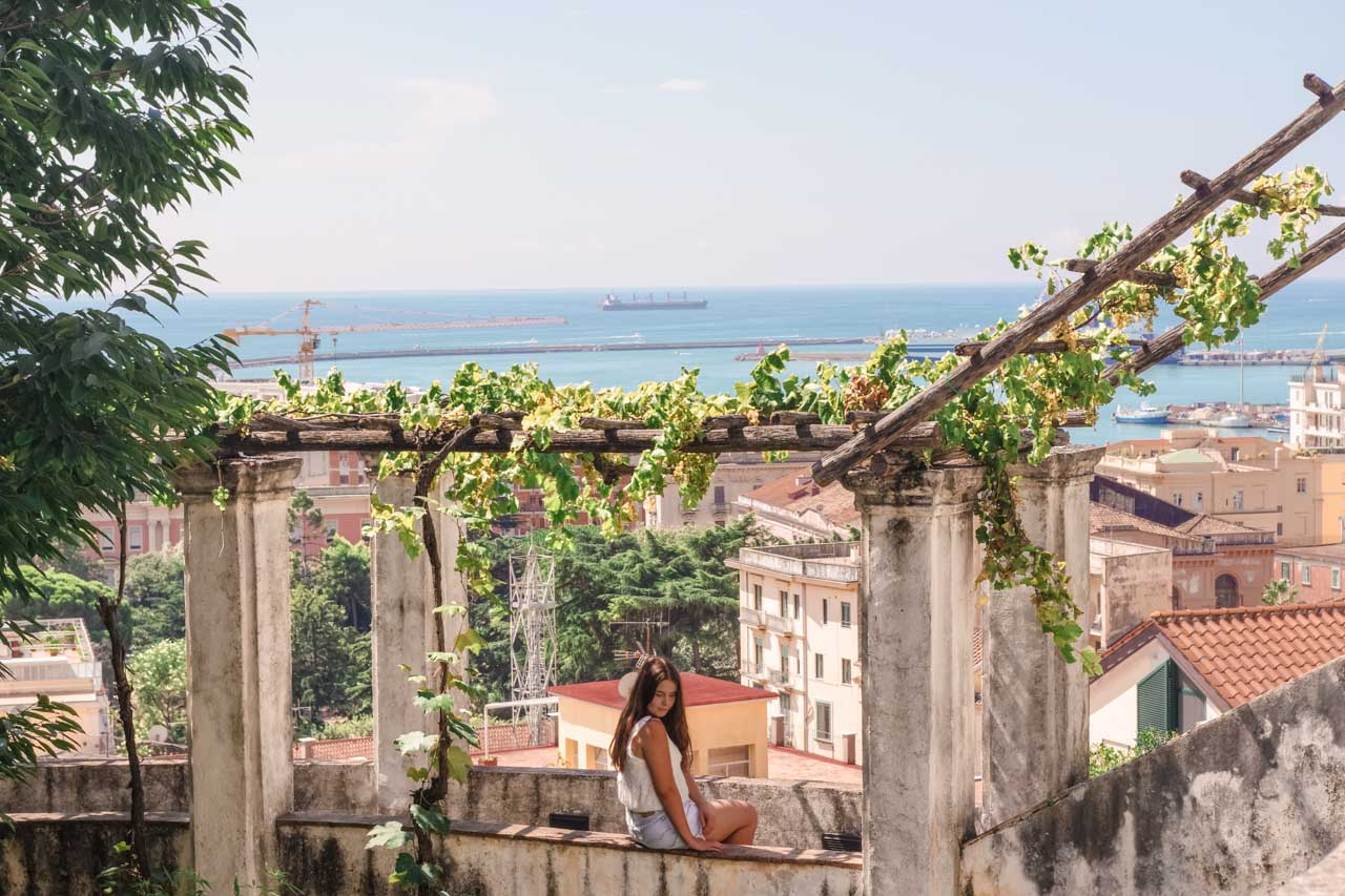 A girl in a white crop top and denim shorts sitting on the ledge of Giardino della Minerva in Salerno, Italy