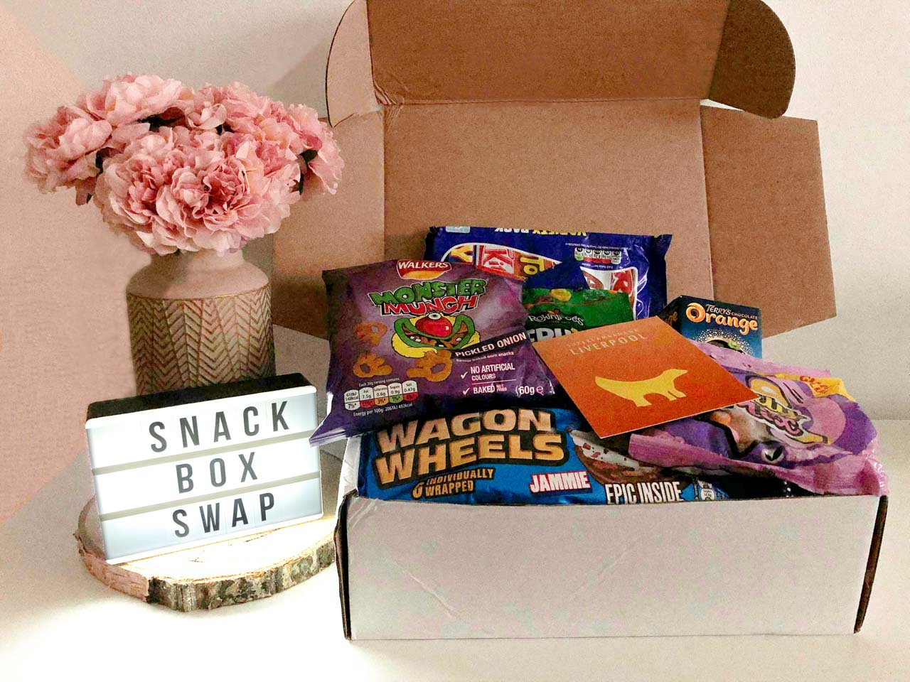 "A cardboard box filled with British snacks next to a vase of peonies and a light box that says ""Snack box swap"""