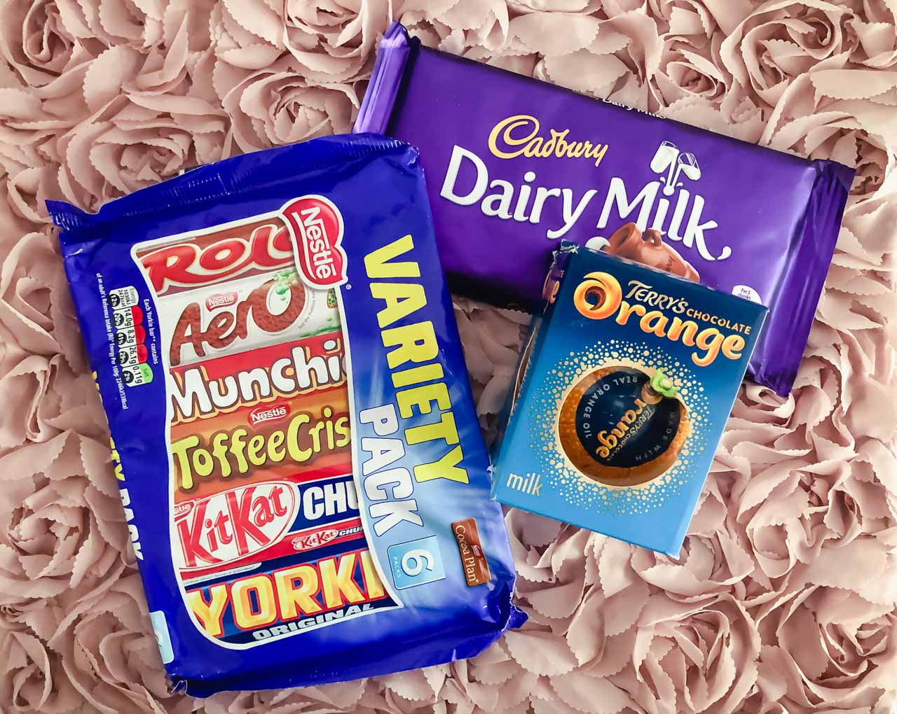 A variety pack of Nestle chocolate bars, a bar of Cadbury Dairy Milk chocolate, and a Terry's Chocolate Orange against a pink background