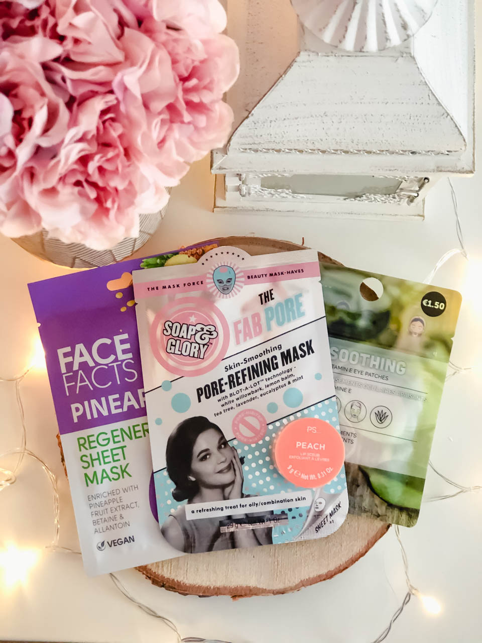 Three face masks from Soap and Glory, Face Facts and Primark on a desk next to a vase of peonies and a wooden lantern