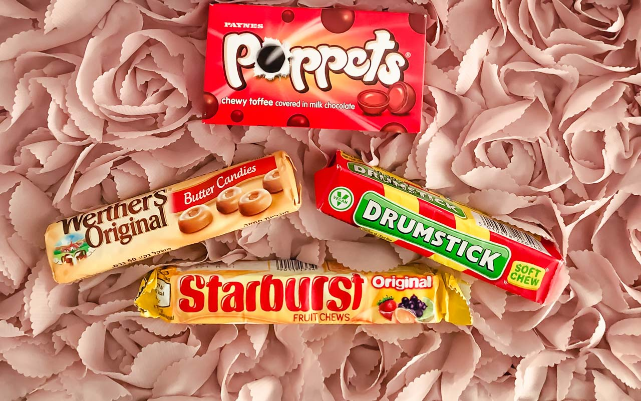 British snacks: Packs of Starburst, Drumstick, Werther's Original and Poppets against a pink background