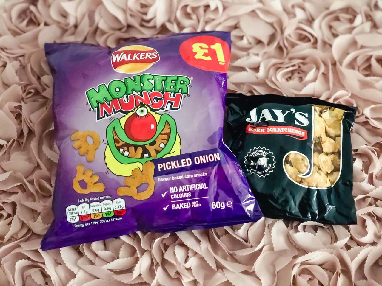 British snacks: A pack of pickled onion Monster Munch and Jay's pork scratchings against a pink background