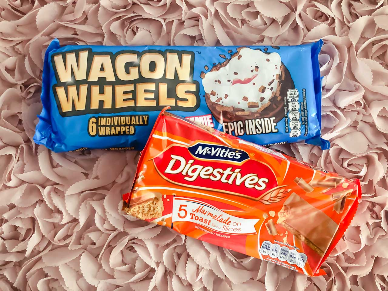 A pack of Wagon Wheels and marmalade on toast Digestives against a pink background