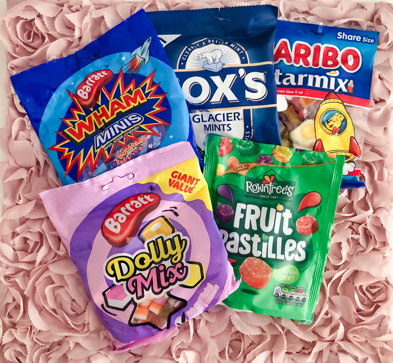 A pack of Wham minis, Fox's Glacier mints, Haribo Starmix, Dolly Mix and Fruit Pastilles against a pink background
