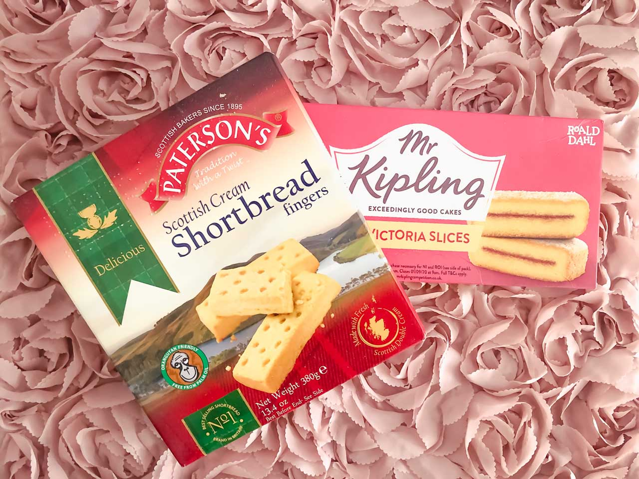 A pack of Scottish Cream shortbread fingers and Mr Kipling Victoria slices against a pink background