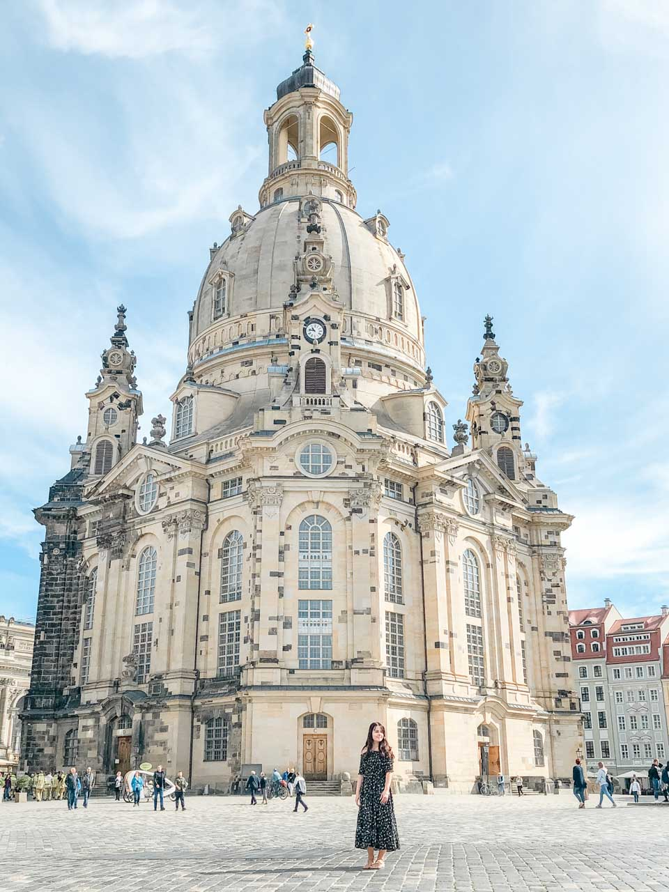 A girl in a maxi dress standing in front of the Frauenkirche in Dresden, Germany