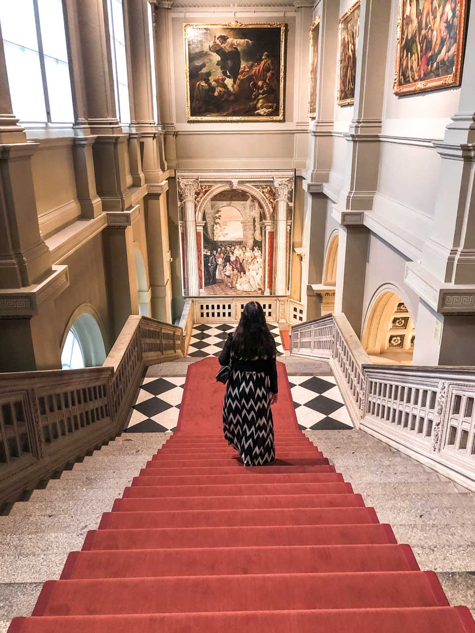 A girl in a maxi dress walking down the stairs inside the Old Masters Picture Gallery (Gemäldegalerie Alte Meister) in Dresden, Germany