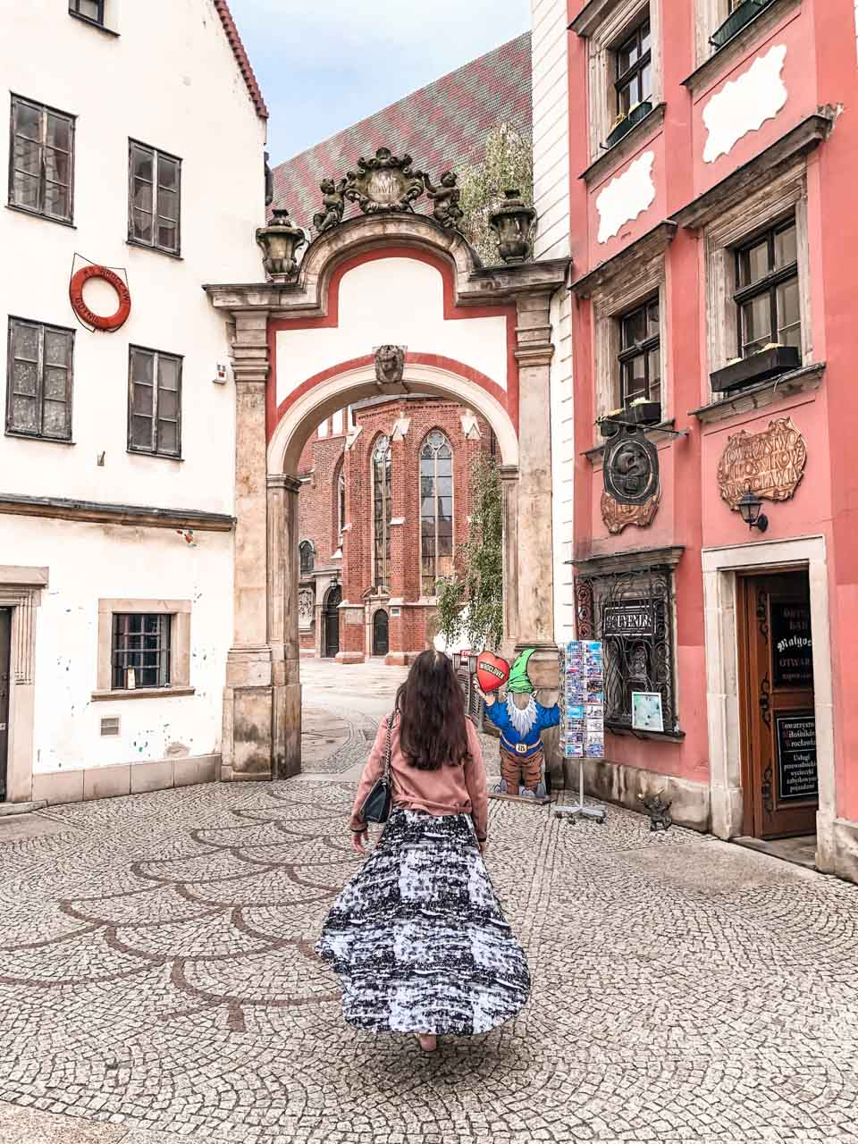 A girl in a maxi dress walking towards the gate between the Hansel and Gretel Houses in Wrocław