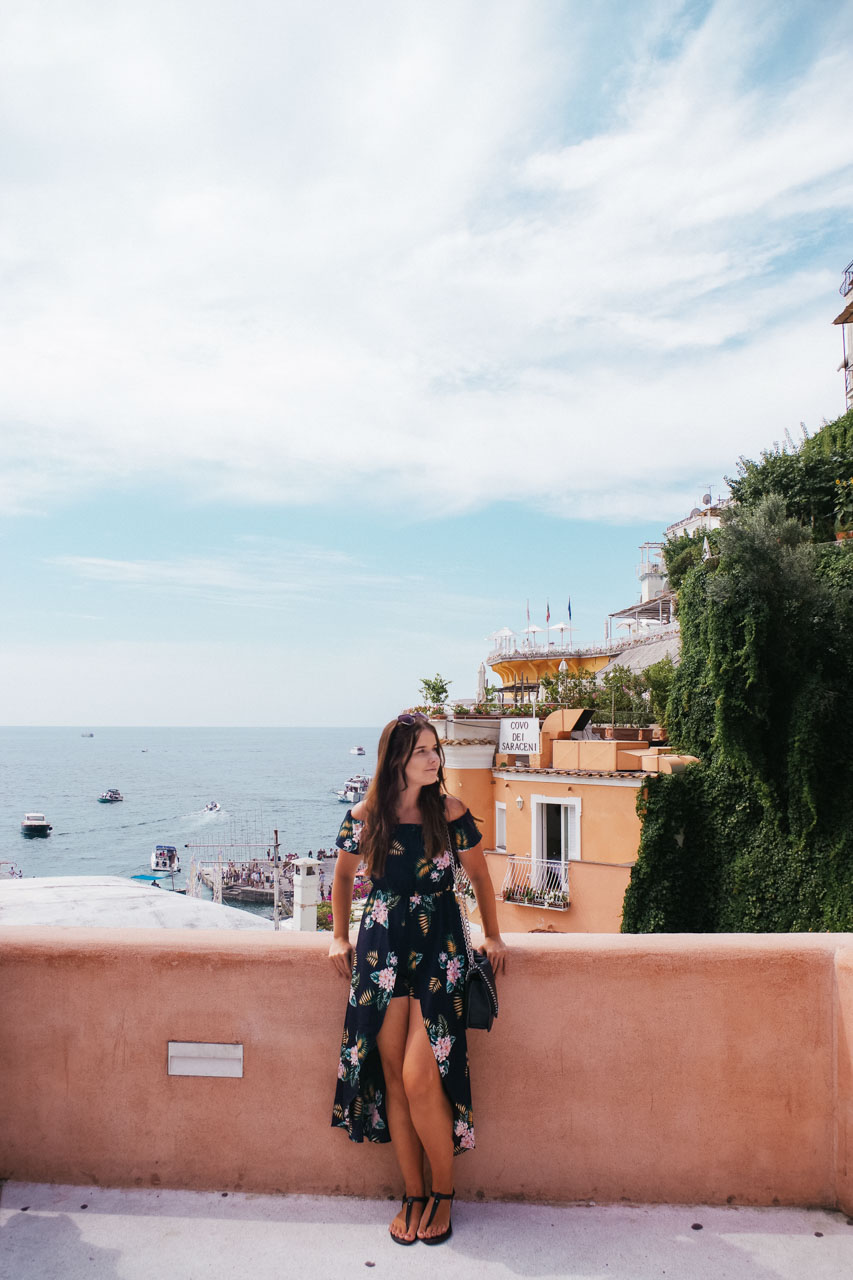 A girl in a floral dress standing in Positano, Italy with the Covo dei Saraceni hotel in the background