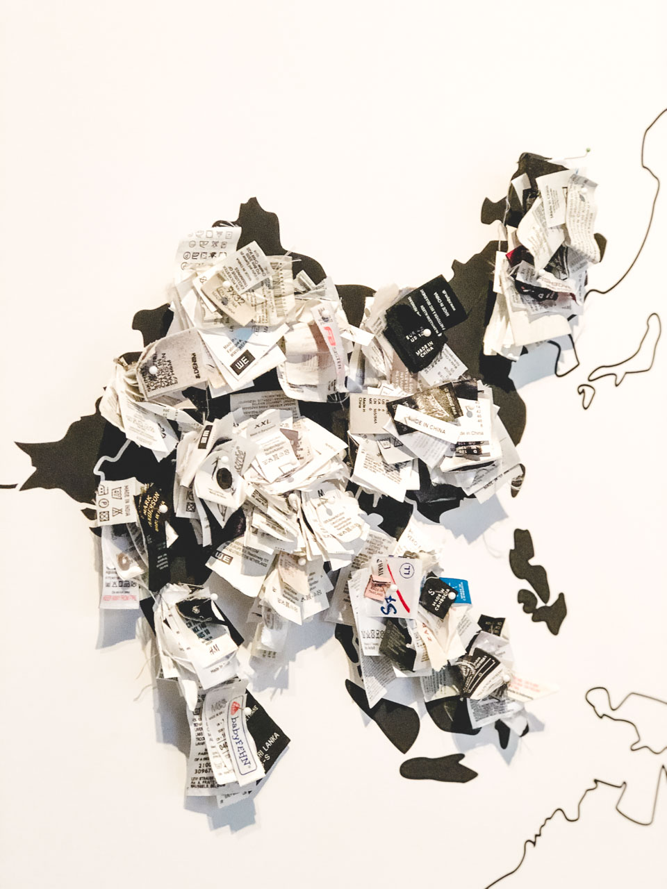 Garment labels glued to a contour world map inside the Museum of European Cultures in Berlin