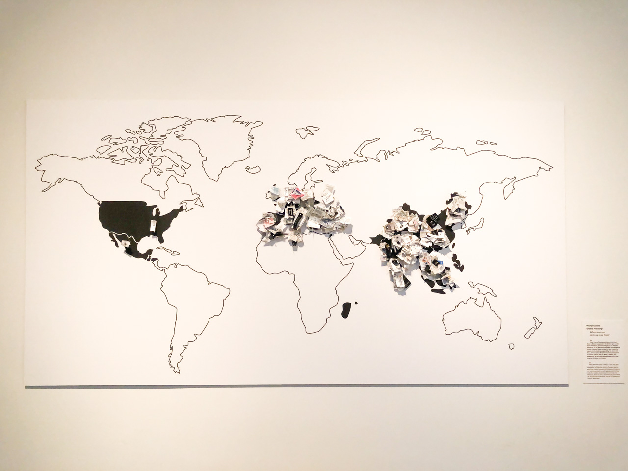 Contour world map with garment labels glued to it inside the Museum of European Cultures in Berlin