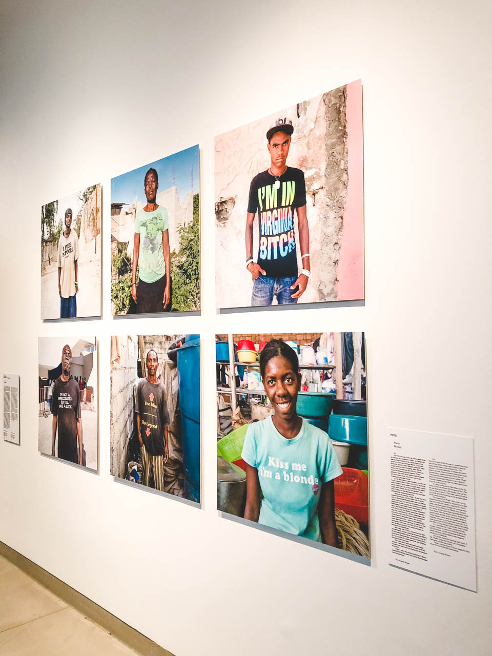 Photos of Haitians wearing T-shirts with silly slogans on display at The Dark Sides of Fashion exhibition