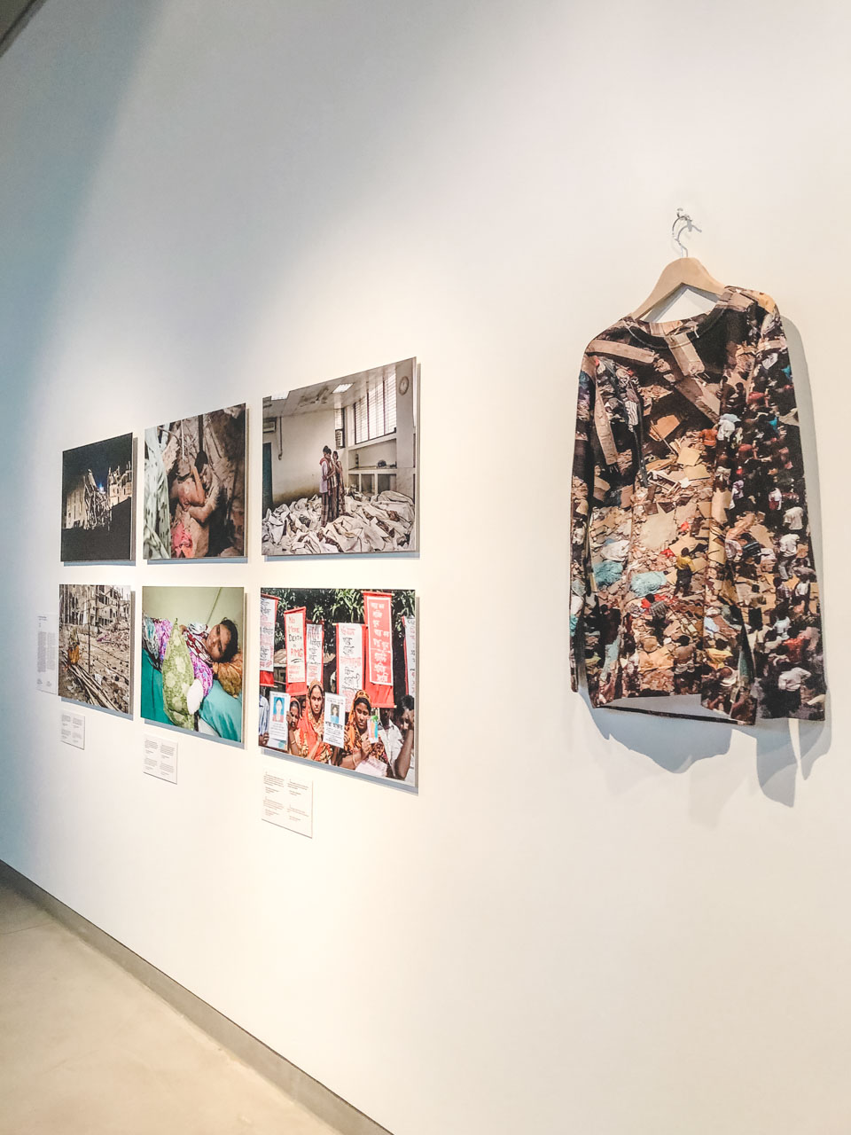 A pullover with a photo of a collapsed Bangladeshi factory printed on it on display at The Dark Sides of Fashion exhibition