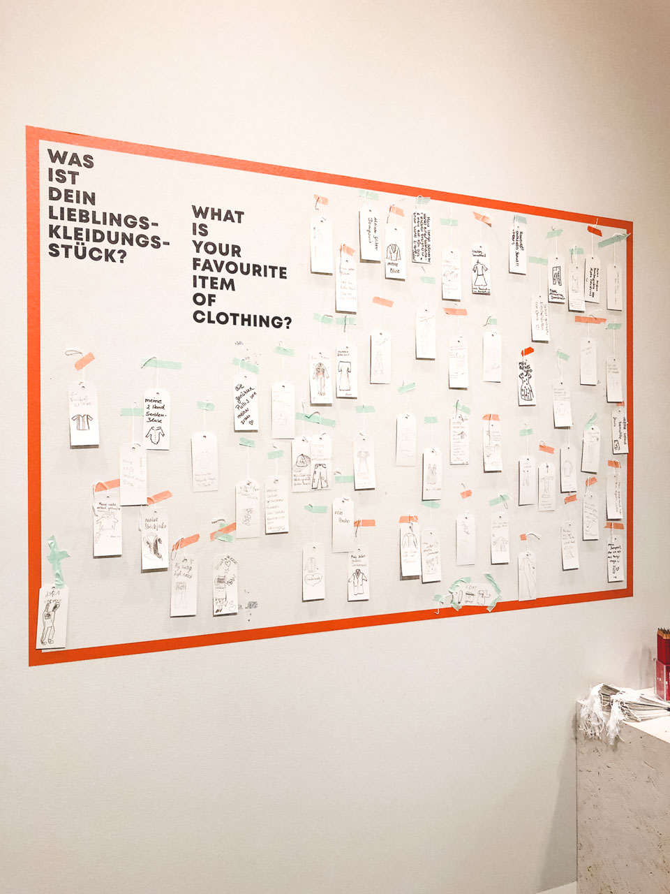"A wall with ""What is your favourite item of clothing?"" written on it and little hangtags with answers pinned to it"