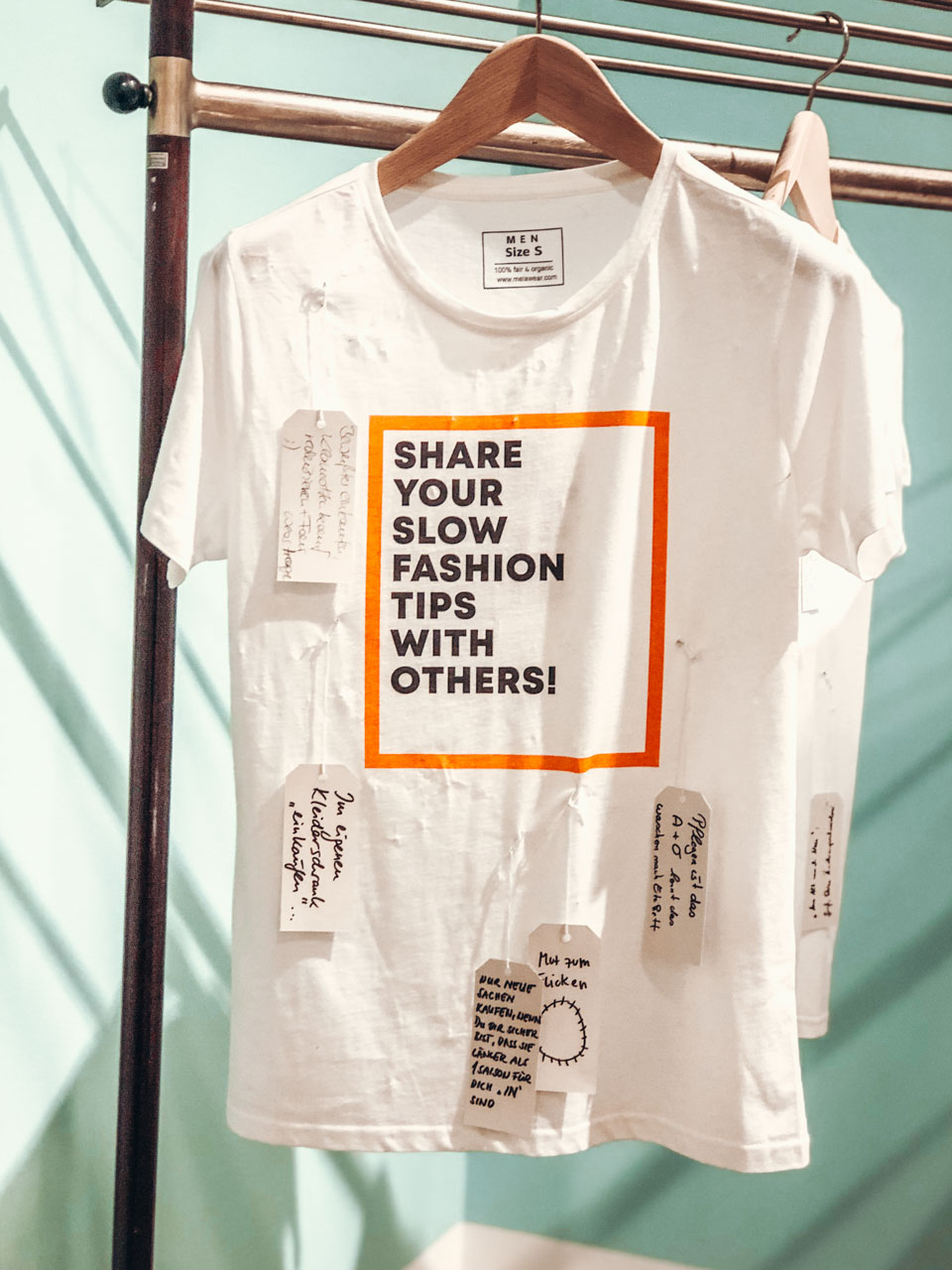 "A T-shirt that says ""Share your slow fashion tips with others"" and little hangtags with the answers attached to it"