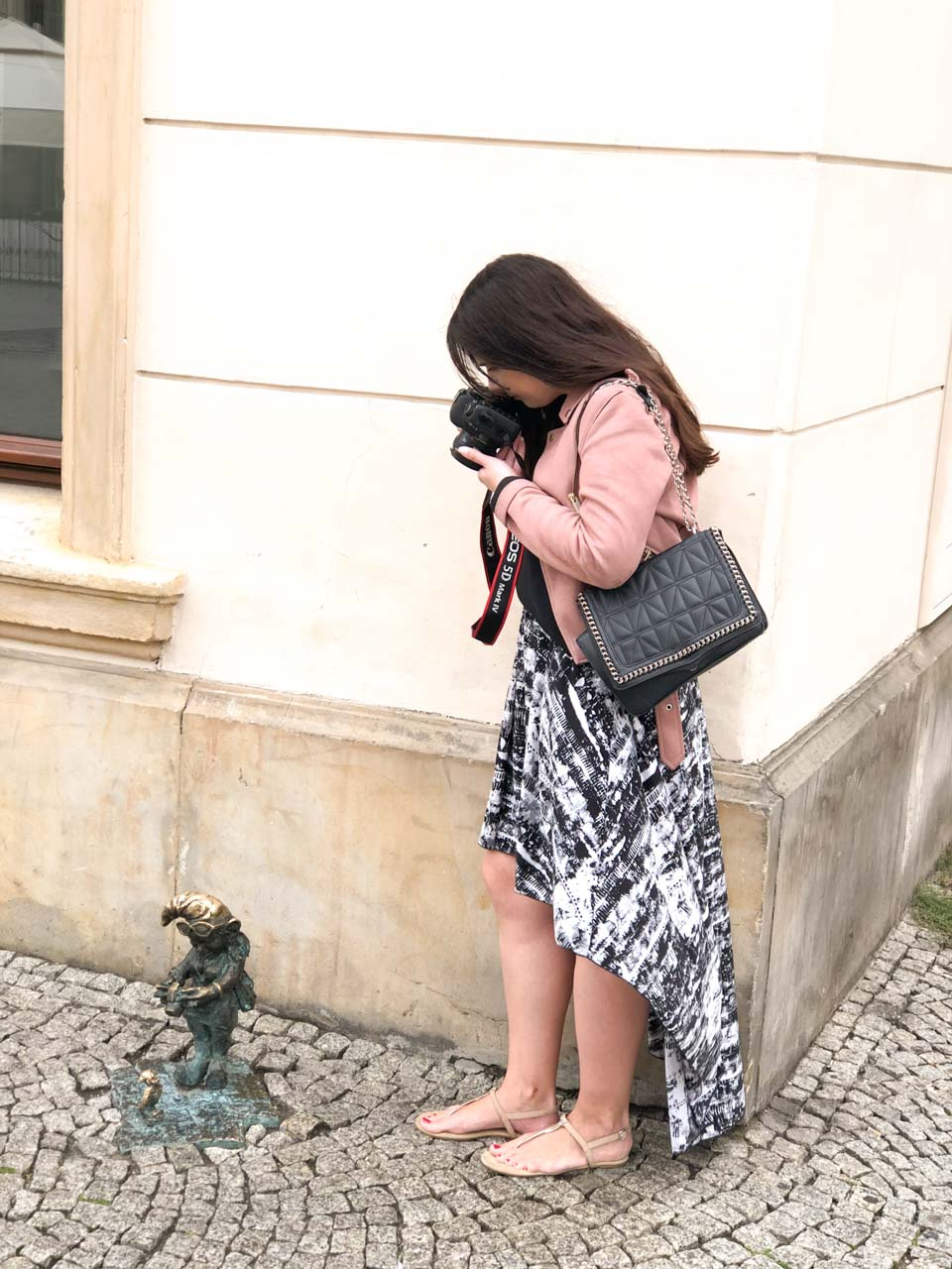 A girl taking a photo of a dwarf statue in Wrocław with her Canon 5D Mark IV DSLR camera