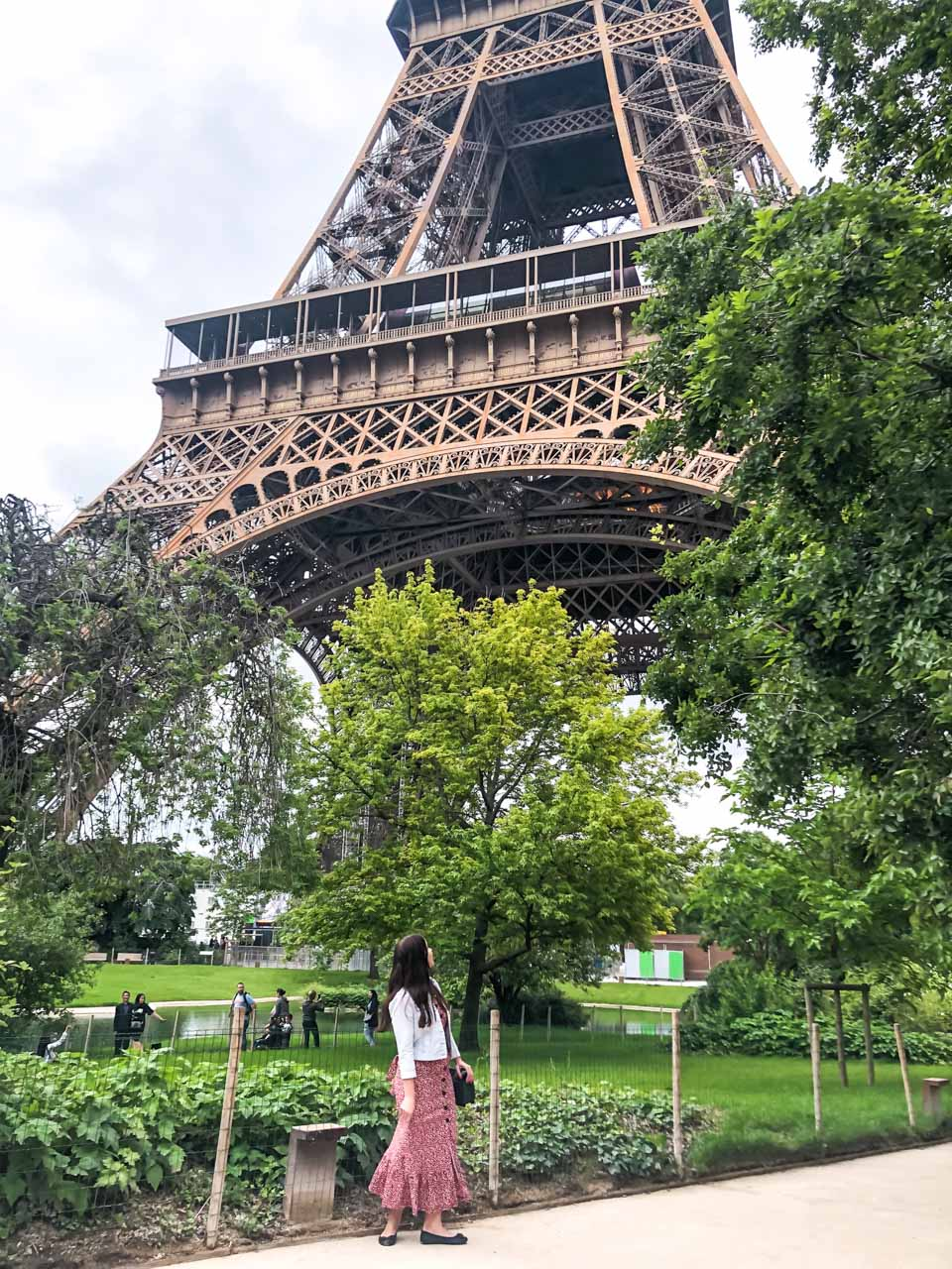 A dark-haired woman in a light denim jacket, a white and red floral midi dress and black ballet flats looking up at the Eiffel Tower in Paris, France as she is standing in the park surrounding it