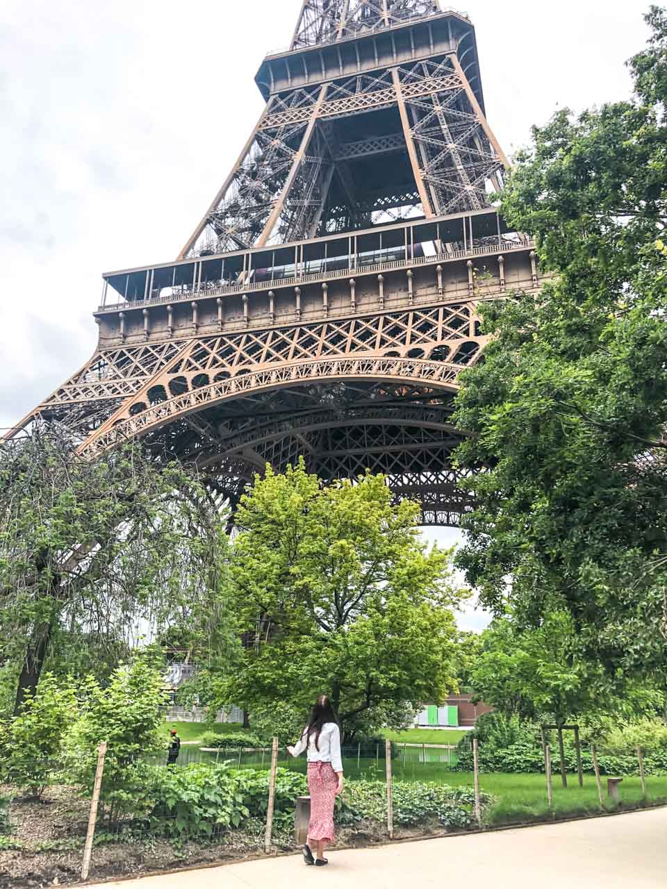 A dark-haired woman in a light denim jacket, a white and red floral midi dress and black ballet flats with her back turned to the camera looking up at the Eiffel Tower in Paris, France as she is standing in the surrounding park