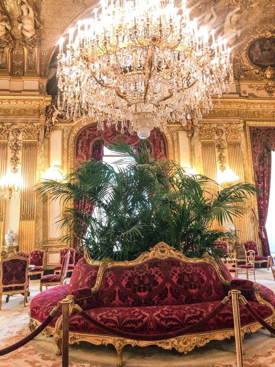 State Drawing Room with a huge golden chandelier and royal furniture including a red borne upholstered seat in the Napoleon III Apartments located in the Richelieu Wing in the Louvre Museum in Paris, France