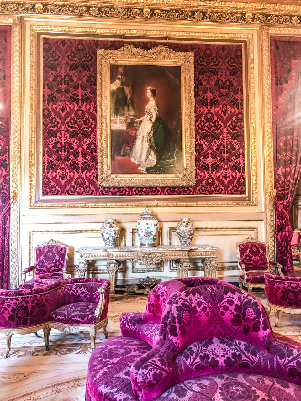 A portrait of Empress Eugenie hanging on the wall inside a room filled with velvet fixtures, gold edgings, red upholstered royal furniture and decorative vases in the Napoleon III Apartments located in the Richelieu Wing in the Louvre Museum in Paris, France