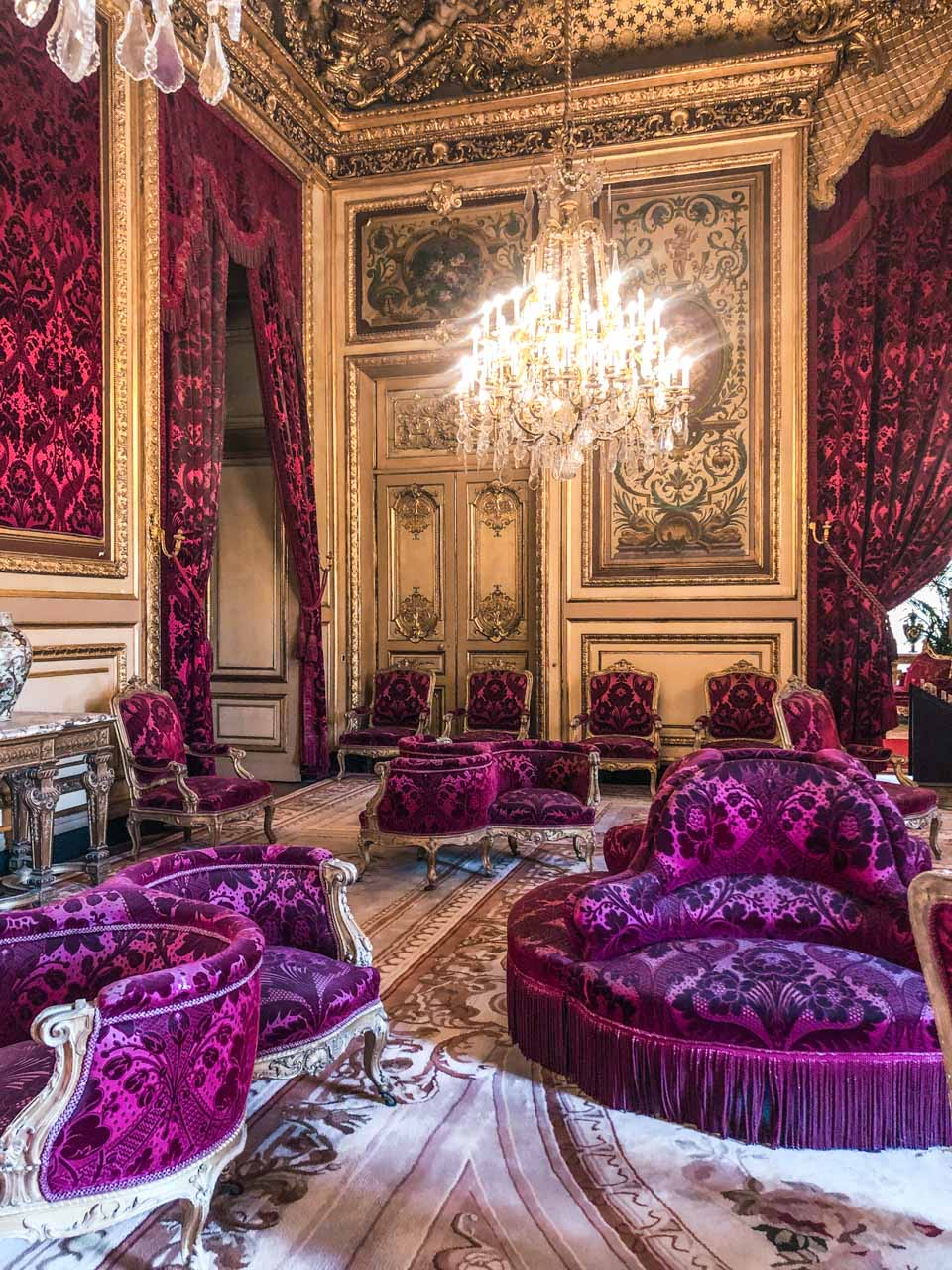 A room filled with velvet fixtures and curtains, gold edgings, red upholstered royal furniture and golden glimmering chandeliers in the Napoleon III Apartments located in the Richelieu Wing in the Louvre Museum in Paris, France