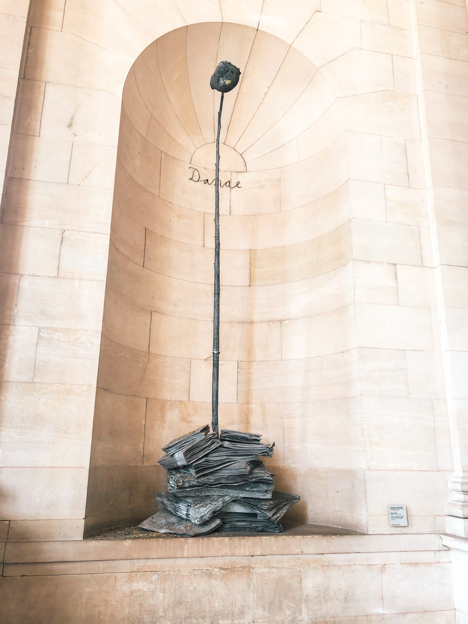 The Danaë sculpture by Anselm Kiefer portraying a blackened depetaled sunflower emerging from a stack of books in the Louvre Museum in Paris, France