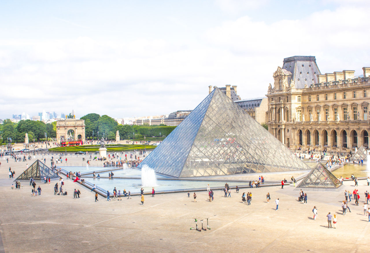 People walking around the Louvre Pyramid with a red double decker hop-on hop-off bus driving past the Arc de Triomphe du Carrousel visible in the distance