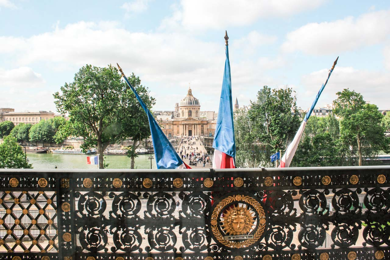 Three French flags hanging on a balcony in the Louvre Museum in Paris, France seen from one of the exhibition halls, with the Institut de France visible in the distance