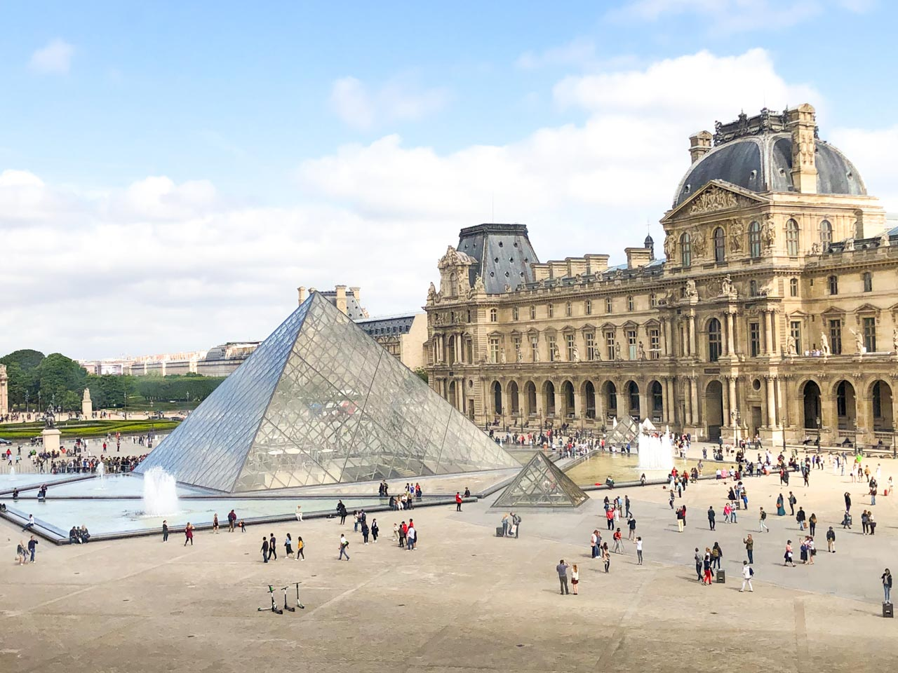 People walking around the Louvre Pyramid seen from the inside of the museum, with the arcades housing Le Café Marly visible on the right side of the photo