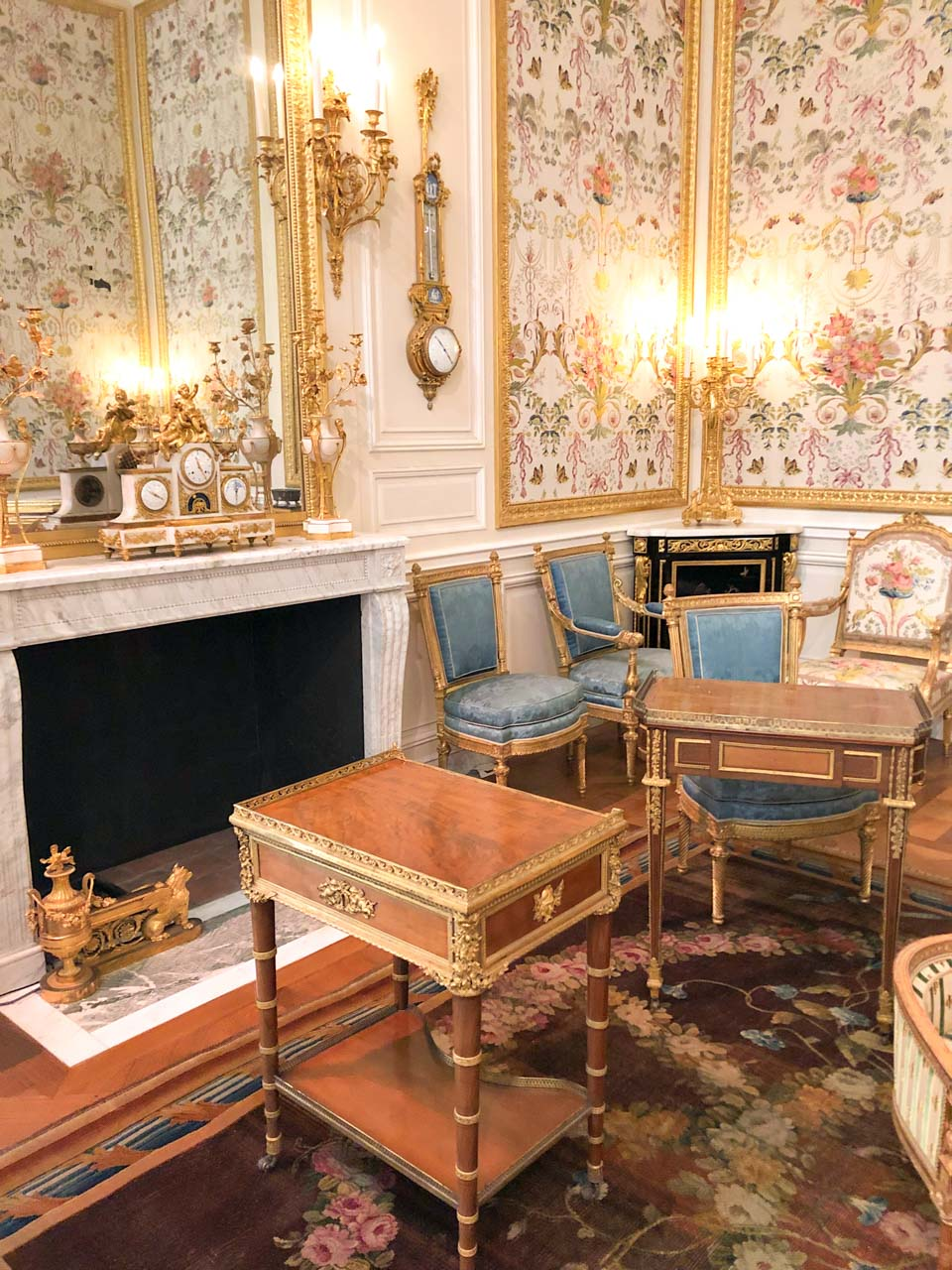"""The Restored """"From Louis XIV to Louis XVI"""" rooms in the Louvre with Baroque wallpapers, wooden cabinets and blue upholstered furniture next to the fireplace area"""