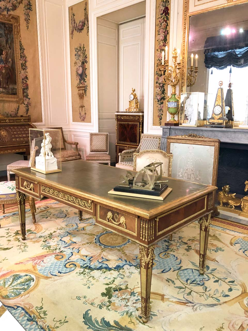 """A beautifully carved wooden desk in the ornately decorated """"From Louis XIV to Louis XVI"""" rooms in the Louvre Museum in Paris, France"""