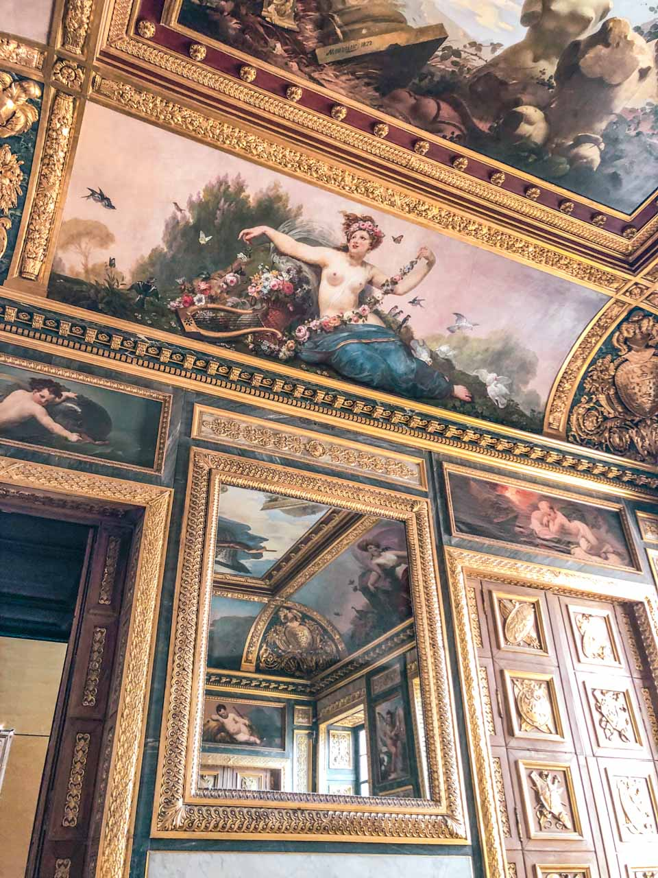 Various frescoes, including one depicting a naked woman, surrounded by gold edgings on the ceiling in the Louvre Museum in Paris, France