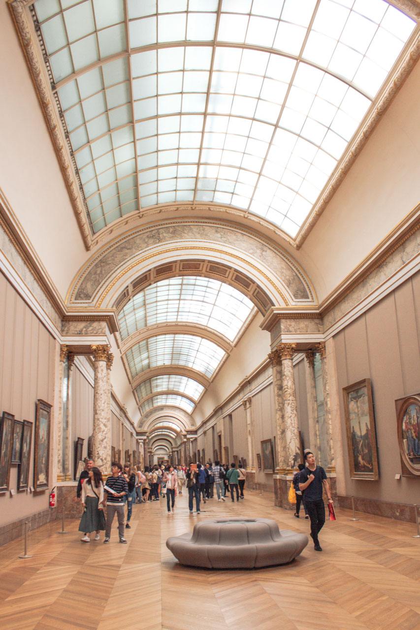 People wandering through the hallways and admiring the paintings hanging on the walls in the Louvre Museum in Paris, France