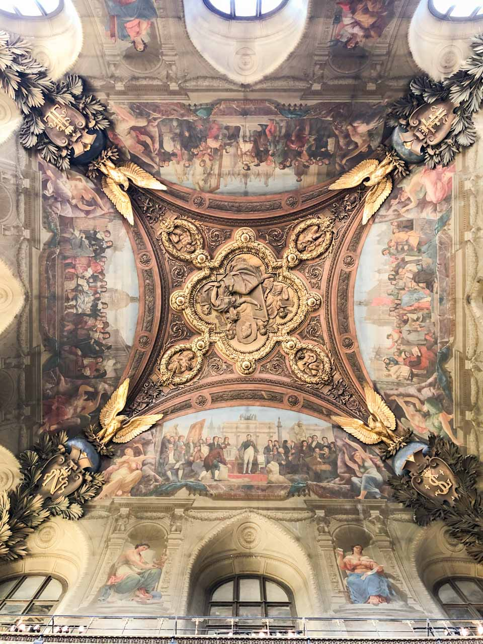 Frescoes on an ornately decorated ceiling in the Louvre Museum in Paris, France