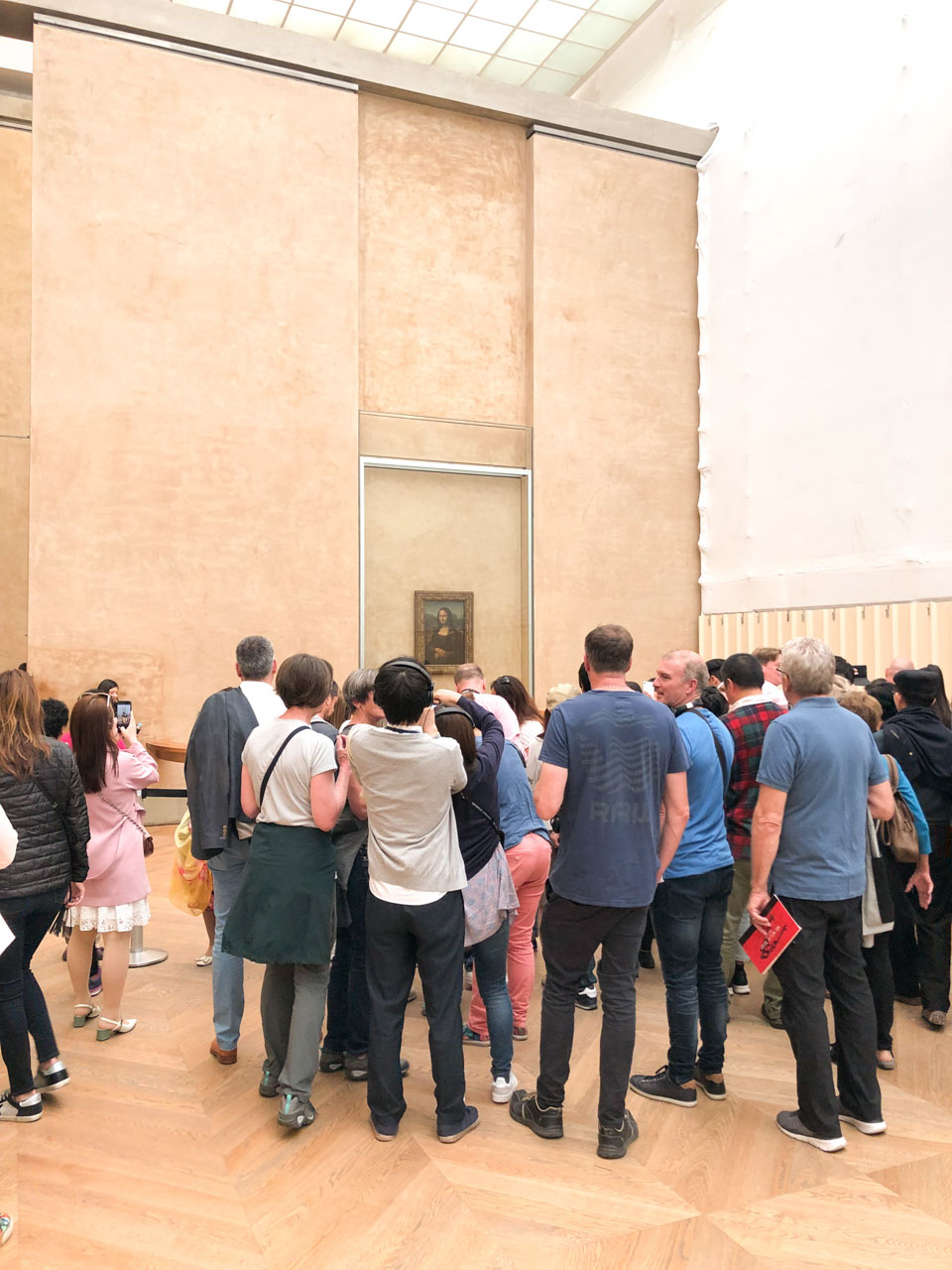 Crowds of people gathered around the Mona Lisa painting by Leonardo da Vinci at the Louvre, looking at and taking photos of the painting