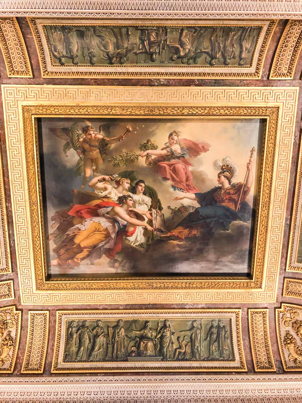 A fresco surrounded by gold edgings on the ceiling in the Louvre Museum in Paris, France