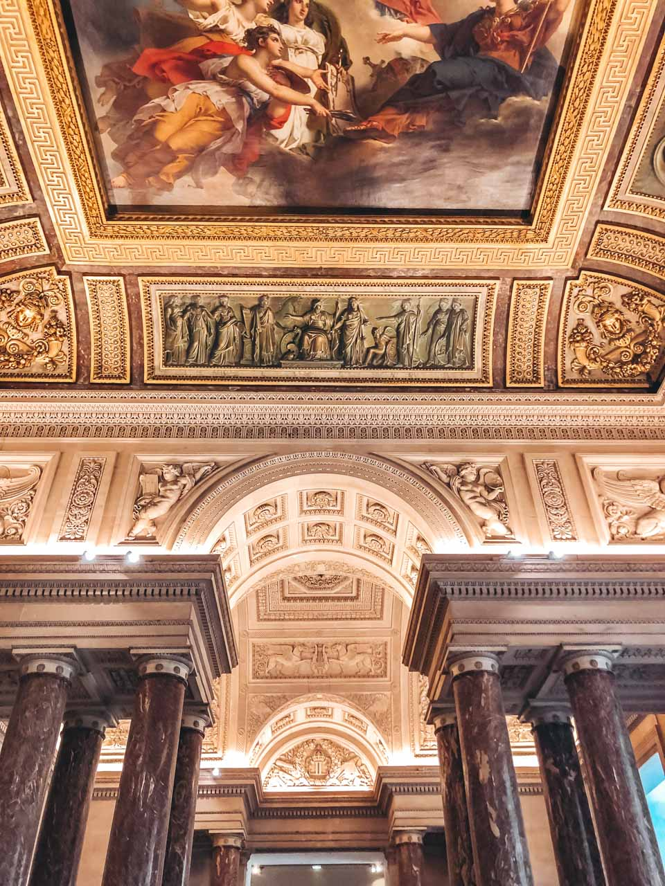 Ceiling art at the Louvre in Paris, France, including a fresco, gilded embellishments, and little carved statues and details