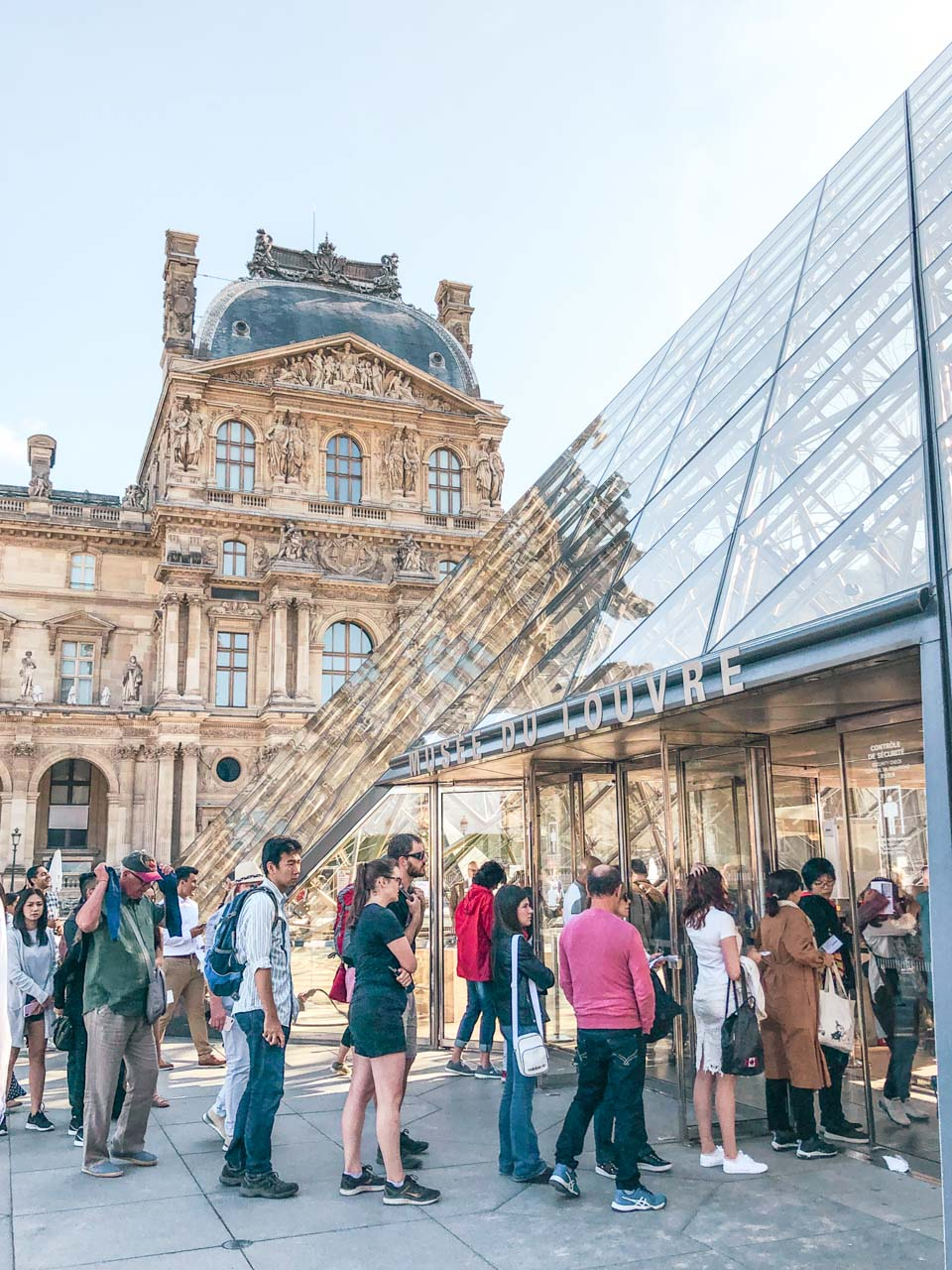 Crowds of tourists queueing outside the glass pyramid to get inside the Louvre Museum in Paris, France