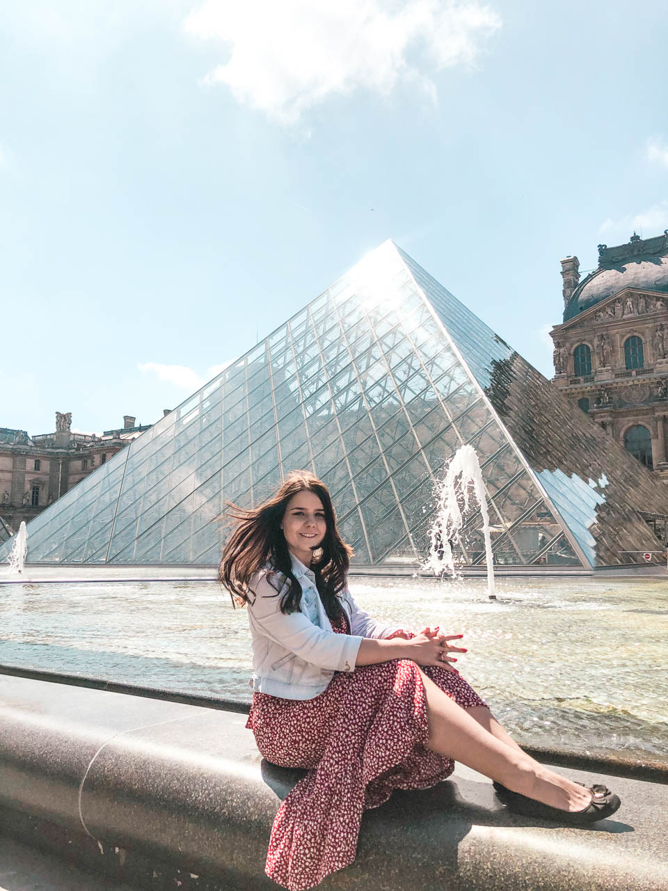 A dark-haired young woman in a denim jacket, a red and white floral dress and black ballet flats sitting on a fountain ledge with the Louvre Pyramid behind her back