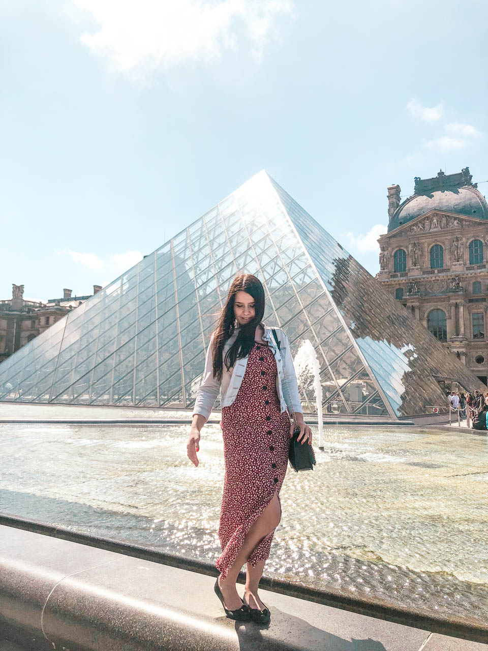 A dark-haired young woman in a denim jacket, a red and white floral dress and black ballet flats standing on a fountain ledge with the Louvre Pyramid behind her back