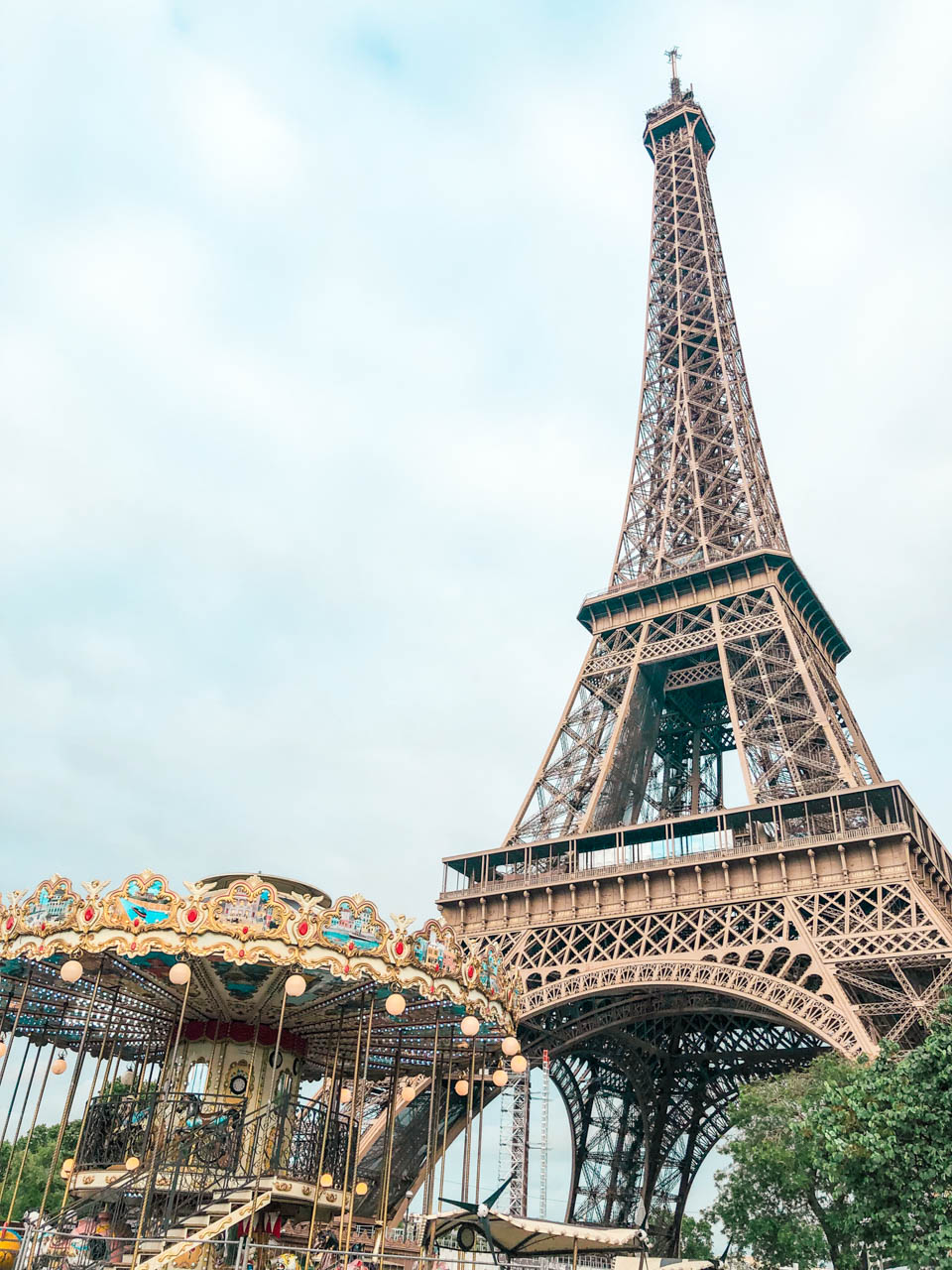 A close-up shot of the Carousel of the Eiffel Tower on the left and the Eiffel Tower on the right