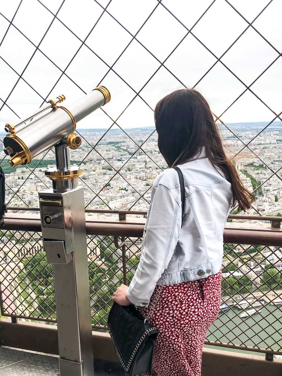 A dark-haired woman in a light denim jacket and a white and red floral dress clutching her black quilted handbag as she is standing next to the telescope on the observation deck at the top of the Eiffel Tower in Paris, France