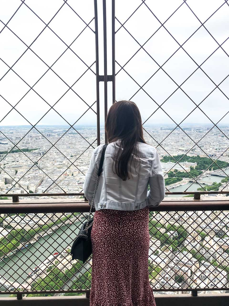 A dark-haired woman in a light denim jacket and a white and red floral dress with her back turned to the camera leaning against the ledge of the observation deck at the top of the Eiffel Tower and admiring the view